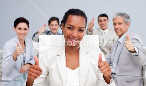 Happy business team celebrating a sucess with thumbs up