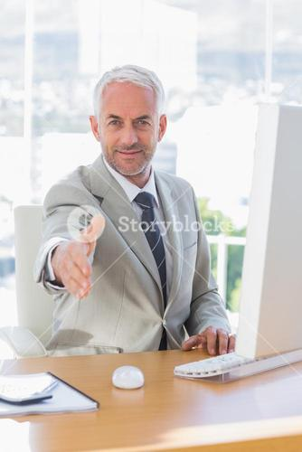 Smiling businessman reaching out for handshake