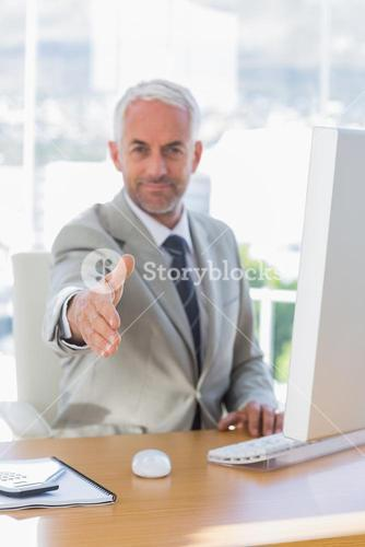 Happy businessman reaching out for handshake