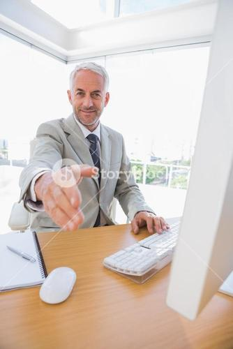 Happy businessman reaching hand out for handshake