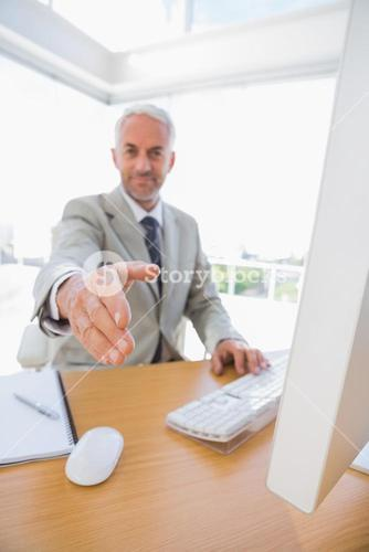 Cheerful businessman reaching hand out for handshake