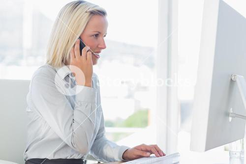 Young businesswoman working on computer on the phone