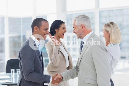 Succesful business team shaking hands and high fiving