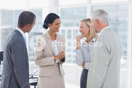 Happy business team chatting and laughing