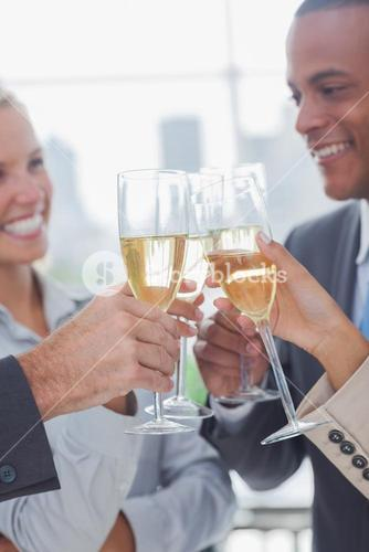 Business team celebrating with champagne and clinking glasses