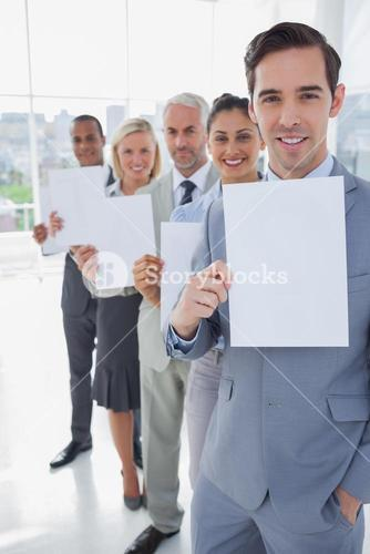 Business team in a line holding white pages