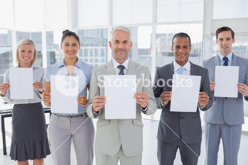 Buisness team holding up blank pages