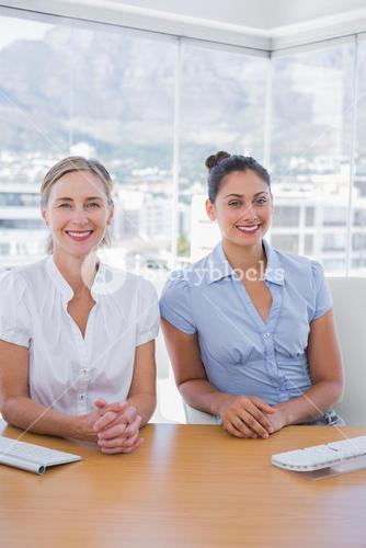 Happy businesswomen sitting side by side
