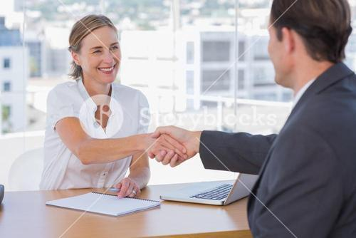 Cheerful interviewer shaking hand of an interviewee