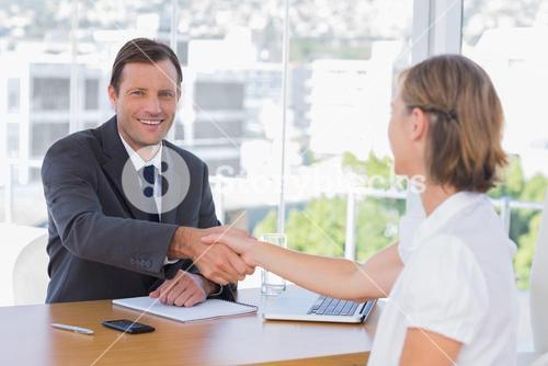 Smiling businessman shaking hand of a job applicant