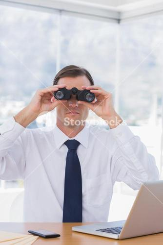 Businessman using binoculars in front of the camera