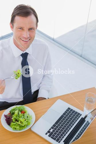 Overhead of a smiling businessman eating a salad