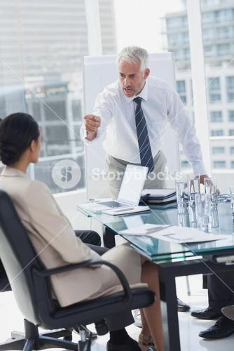 Furious boss pointing at an employee