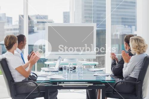 Business people applauding at a screen