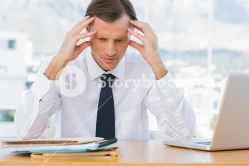 Worried businessman holding his head