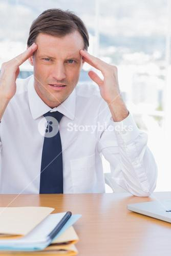 Stressed businessman holding his head