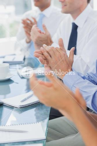 Business people clapping together
