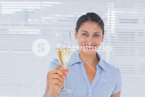 Businesswoman holding flute of champagne