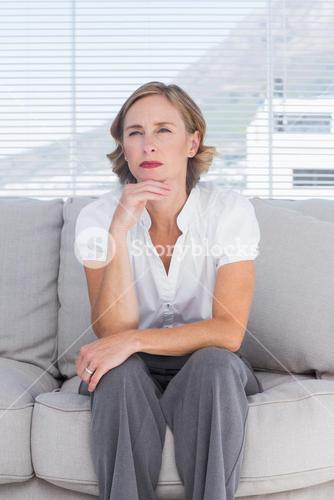 Thinking businesswoman sitting on couch