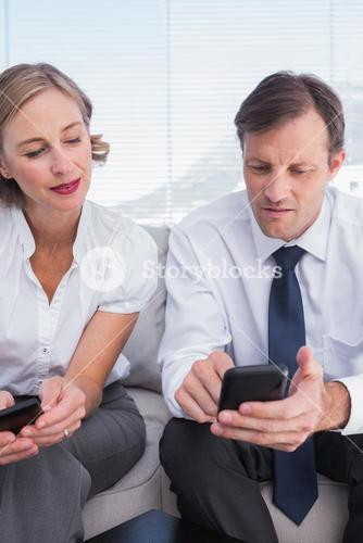 Business partners using their mobile phones