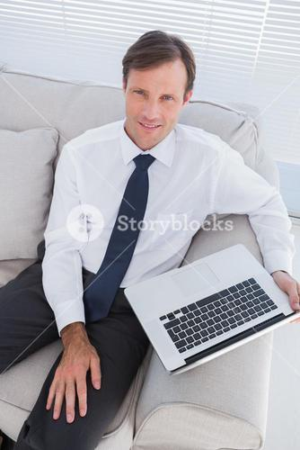 Portrait of handsome businessman sitting on couch