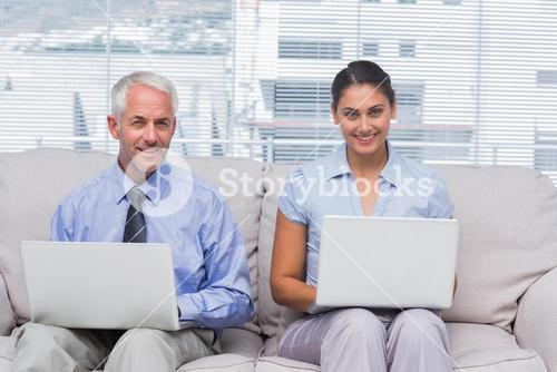 Business people sitting on sofa using their laptops and smiling at camera