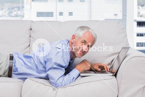 Happy businessman lying on sofa with laptop