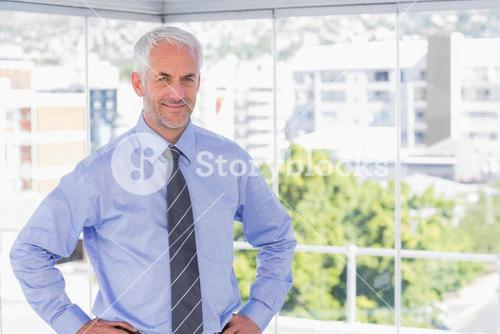 Businessman smiling at camera with hands on hips