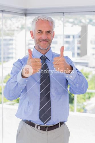 Businessman smiling with thumbs up