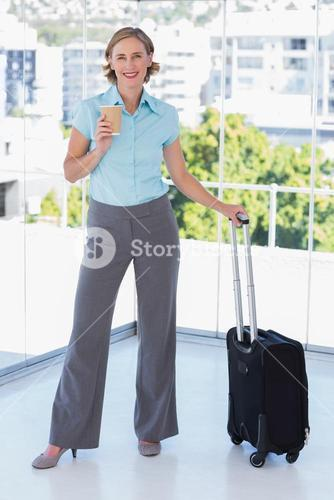 Businesswoman with coffee and suitcase
