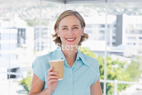 Businesswoman holding disposable coffee cup