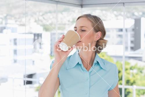 Businesswoman drinking from disposable coffee cup