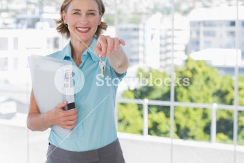Estate agent showing house keys and smiling at camera