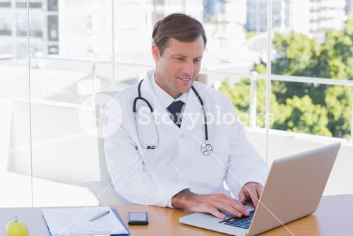 Happy doctor working on a laptop