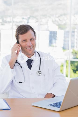 Smiling doctor phoning in his office