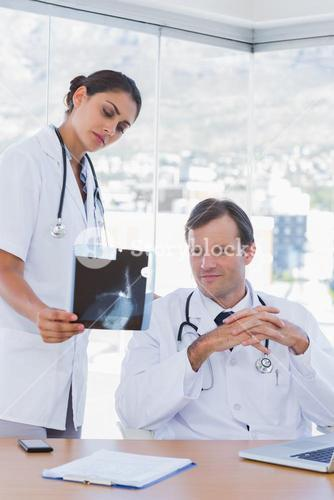 Attractive doctor showing a x ray to a colleague