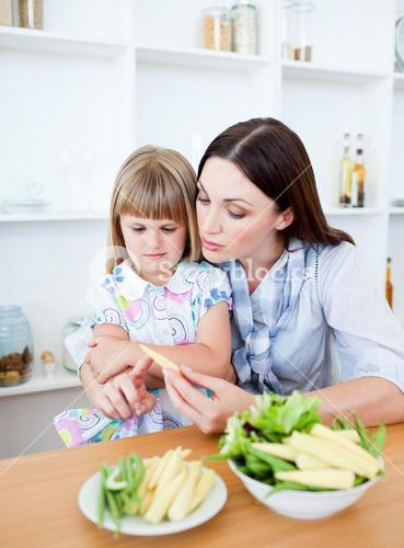 Dissatisfied little girl eating vegetables with her mother