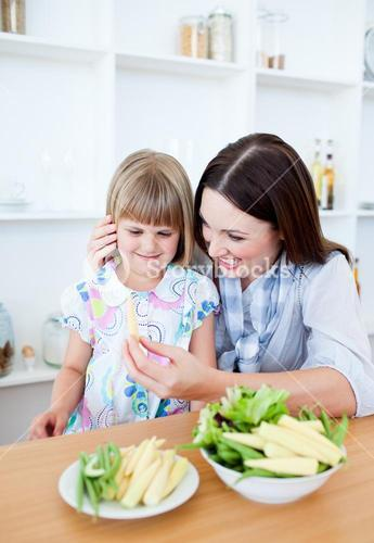 Smiling little girl eating vegetables with her mother