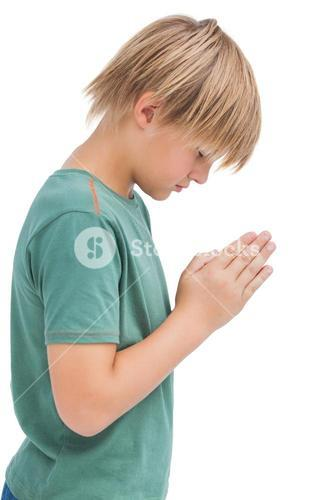 Little boy praying with bowed head