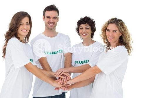 Smiling volunteer group piling up their hands