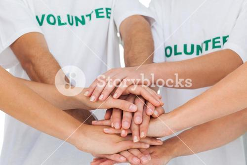 Volunteers piling up their hands together