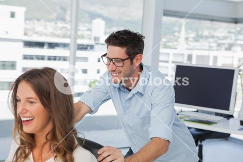 Smiling designers playing on a swivel chair