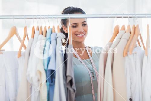 Attractive fashion designer looking at clothes