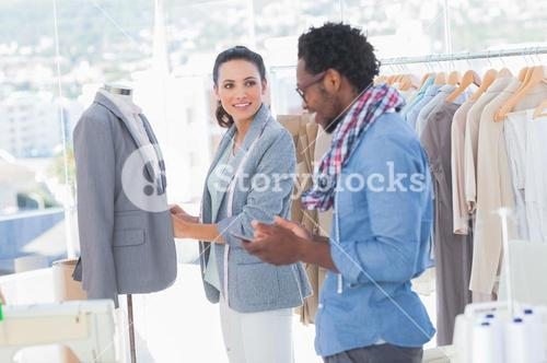 Fashion designers adjusting blazer