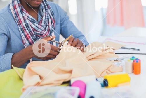 Fashion designer cutting textile