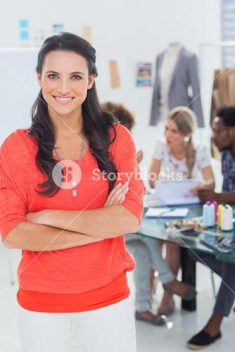 Pretty fashion designer with arms crossed in bright office