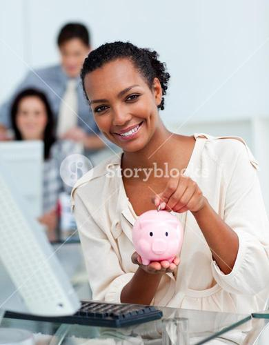 Smiling businesswoman saving money in a piggybank