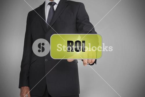 Businessman selecting green tag with the word roi written on it