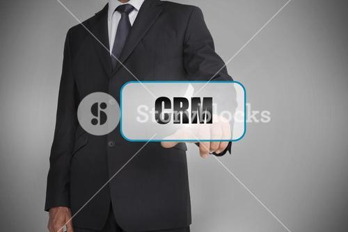 Businessman touching white tag with the word crm written on it