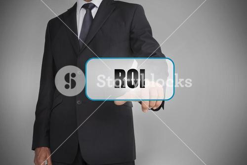 Businessman touching white tag with the word roi written on it